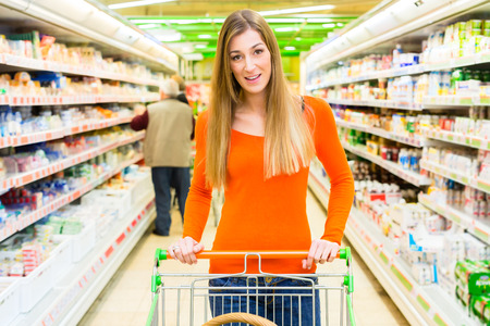 shopping trolley: Woman driving shopping cart while grocery shopping in supermarket Stock Photo