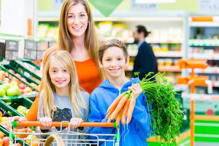 ni�os de compras: Familia seleccionando frutas y verduras mientras realizan sus compras en el supermercado