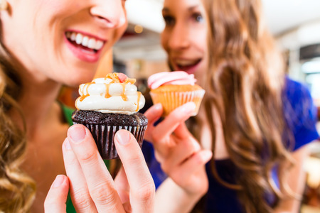 cakes and pastries: Friends having fun and eating muffins at bakery or pastry shop Stock Photo