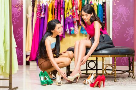 tienda de zapatos: Señora asiática de ventas joven ofreciendo zapatos de mujer en tienda de moda