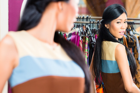 Asian young woman choosing dress in fashion store looking at herself in the mirror photo