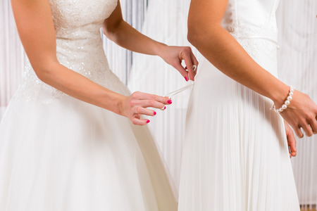 bridal gown: Mujeres que intentan en el vestido de novia juntos en la tienda de moda nupcial