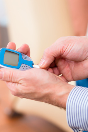 blood sugar: Man with adult onset diabetes measuring blood sugar with indicator