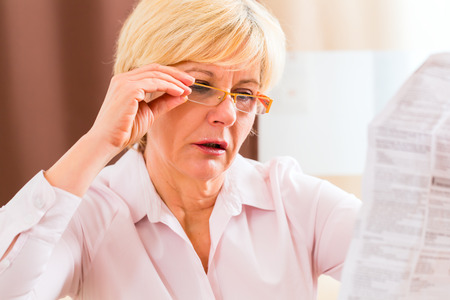 side by side: Old woman reading  medicament package insert at home with glasses