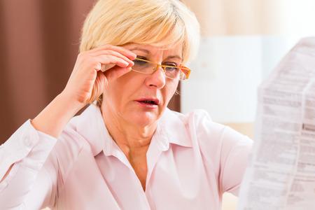Oude vrouw lezend medicament bijsluiter thuis met een bril