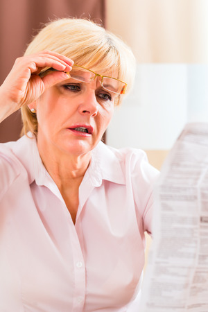 side effect: Old woman reading  medicament package insert at home with glasses