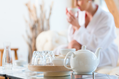 Woman in bath robe drinking tea in wellness spa relaxation room Stockfoto
