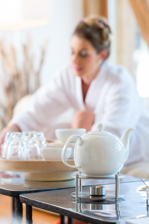 bath gown: Woman in bath robe drinking tea in wellness spa relaxation room Stock Photo