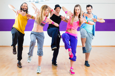 hip hop dance: Group of men and women dancing zumba fitness choreography in dance school