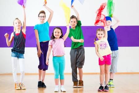 dancing pose: Children dancing modern group choreography with scarfs Stock Photo