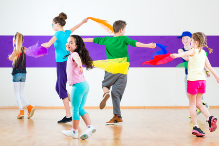 Children dancing modern group choreography with scarfs Stockfoto