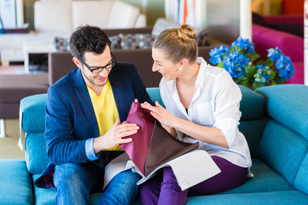 furniture store: Young couple selecting together seat cover for sofa in furniture store