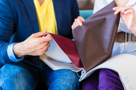 furniture shop: Young couple selecting together seat cover for sofa in furniture store