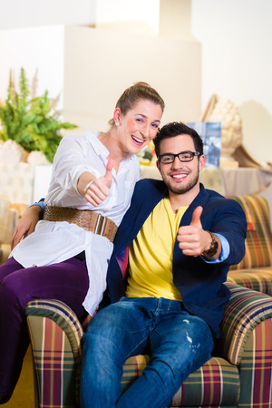 specialised: Young couple selecting together armchair in furniture store Stock Photo