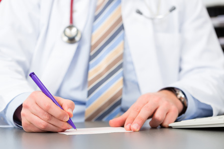 medical notes: Young doctor writing medical prescription in surgery at desk
