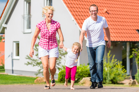 Family of Parents and child walking in front of home in village or suburb photo