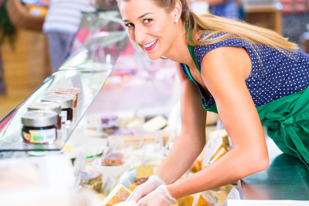 Saleswoman working at counter in groceries shop photo