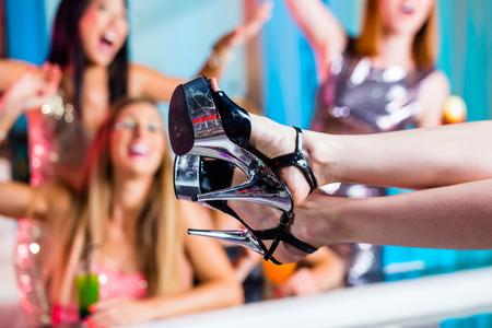 striptease: Friends watching striptease in strip club grabbing at female stripper