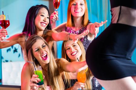 Friends watching striptease in strip club grabbing at female stripper photo