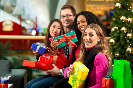 Diversity group of four people - Caucasian, black and Asian - sitting with Christmas presents and bags in a shopping mall in front of a Christmas tree with baubles photo