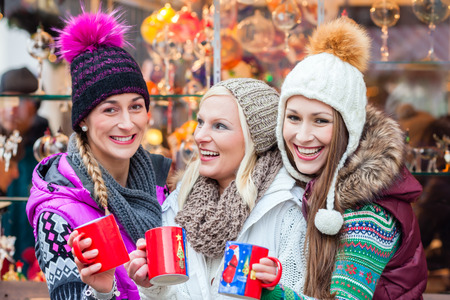 mulled: Woman drinking mulled wine in mug on German Christmas Market Stock Photo