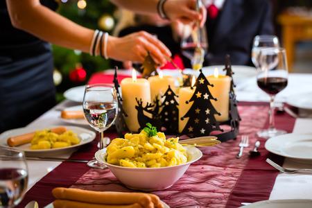 cena navide�a: Familia que celebra la v�spera de Navidad con los embutidos tradicionales de la cena Wiener y ensalada de papa, la mama est� llenando las placas