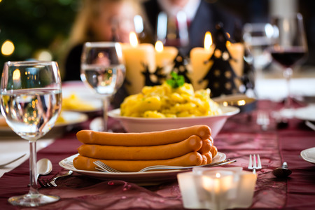 Family celebrating Christmas eve with traditional dinner Wiener sausages and potato salad, mom is filling the plates photo