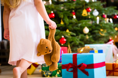 Girl wearing night dress with Christmas gift and teddy bear photo