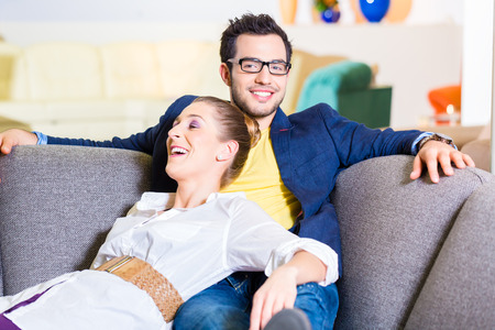furnish: Young couple selecting together sofa in furniture store to furnish home