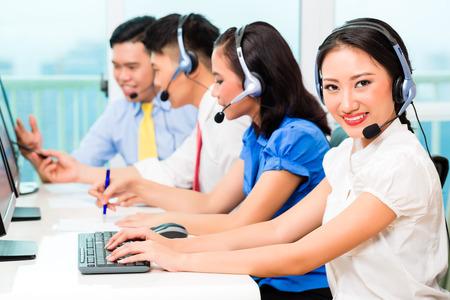 llamando: Equipo de agente de call center chino asiático en el teléfono