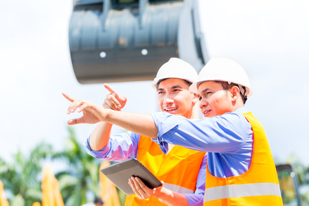 Asian engineer controlling construction machinery of construction site or mining company photo