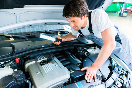 Auto mechanic working in car service workshop Stock Photo