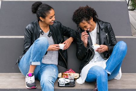 teenagers laughing: Two north African teen friends drinking together coffee outside Stock Photo