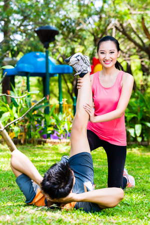 Asian Chinese woman helping man with stretching exercises in park for fitness photo