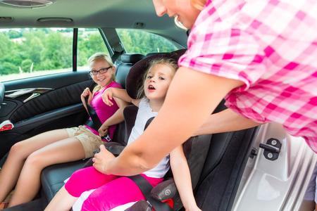 enfant banc: M�re flambage sur l'enfant dans le si�ge de s�curit� de voiture Banque d'images