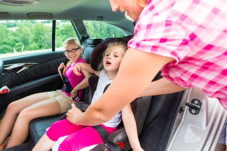 Mother buckling up on child in car safety seat