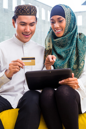 Asian Muslim man and woman shopping online paying with credit card on tablet PC photo