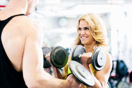Man and woman in fitness gym lifting dumbbells looking at each other photo