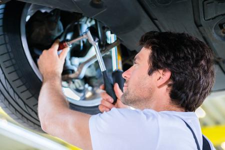 absorber: Mechanic working in car workshop on wheel