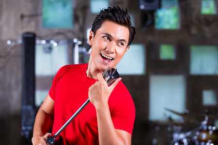 asian produce: Asian professional musician recording new song or album CD in studio