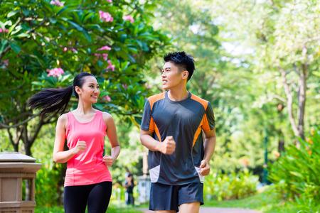 hacer footing: Hombre chino asi�tico y una mujer corriendo en el parque de la ciudad Foto de archivo