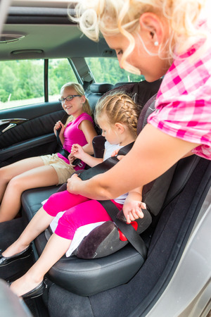 Mother buckling up on child in car safety seat photo