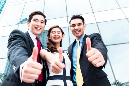 Asian business woman and men outside in front of building Stock Photo