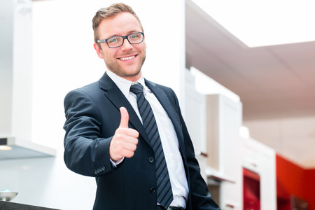 furniture store: Salesman for domestic kitchen in studio or furniture store Stock Photo
