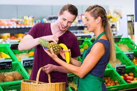 oficinista: Hombre consultar empleado de un supermercado orgánico mientras realizan sus compras Foto de archivo