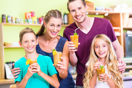 Parents and children drinking smoothie or juice in domestic kitchen photo
