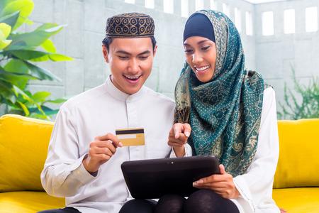 Musulman et asiatique femme achats en ligne payer par carte de crédit sur tablette PC