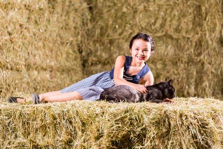 hayloft: Bavarian girl playing with cat on hayloft Stock Photo