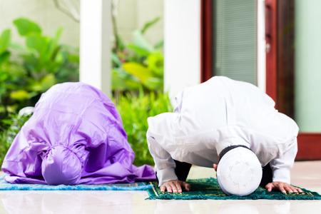 アジアのイスラム教徒のカップル、男と女、トロピカル ガーデンの前に彼らの家の祈りのカーペットの上に座っての家で祈っています。 写真素材