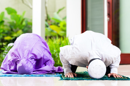 Asian Muslim couple, man and woman, praying at home sitting on prayer carpet in their house in front of the tropical garden photo